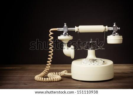 Vintage white rotary telephone on table against black background - stock photo