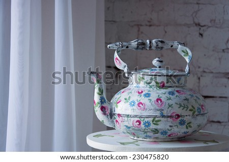 Vintage white tea pot with floral pattern standing on the table - stock photo