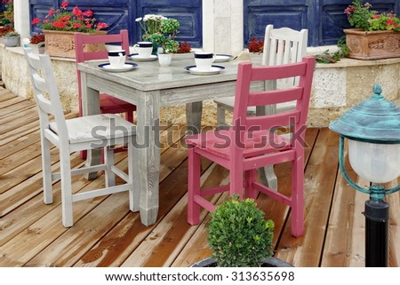 Vintage White Wooden Dining Table And Chairs On The Wet Wood Patio Floor Near Rustic Blue House Wall