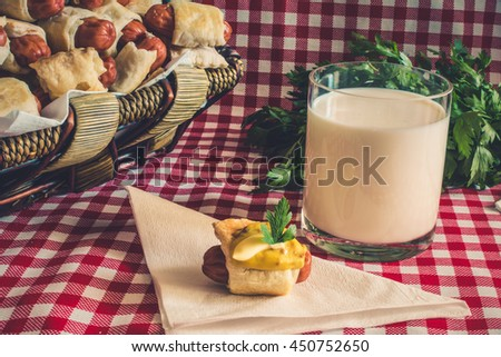 Vintage: Wicker basket with artisan mini hot dogs (Sausage in the dough) with sausage on a napkin covered in mustard, mayonnaise and a glass of fresh cow's milk of the village, on a plaid background - stock photo