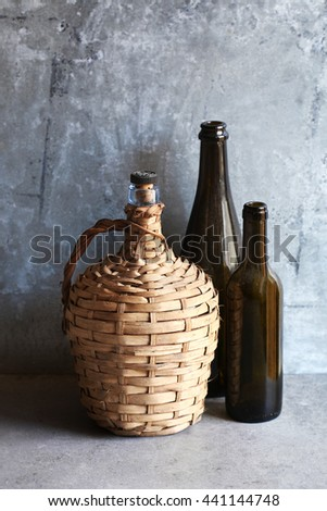 Vintage wicker demijohn and two empty bottles over a metal background