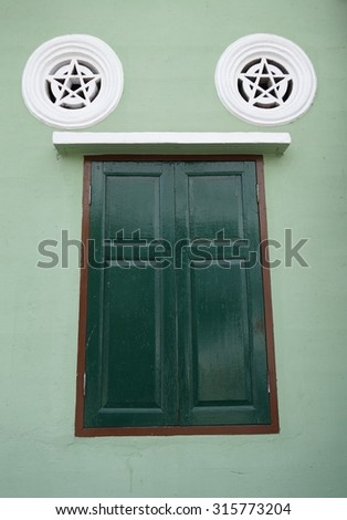 Vintage window and air passage of building exterior in old town Trang, Thailand - stock photo