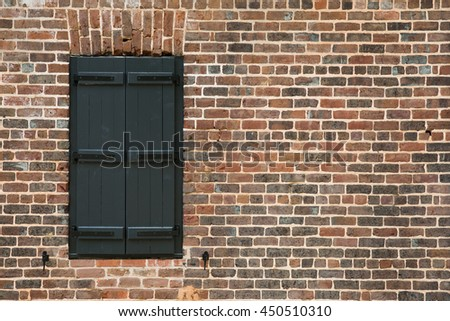 Vintage window architecture element with black shutters on a red brick wall in darker tones
