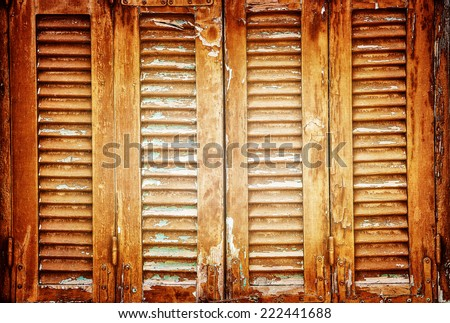 Vintage windows shutters background, closed aged wooden shutters, abstract rustic backdrop, retro house facade, old fashion building detail - stock photo