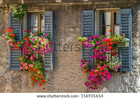 Vintage windows with open wooden shutters and fresh flowers - stock photo