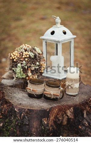 Vintage winter floral composition with lantern, candle, bouquet and 2 cups of tea - stock photo