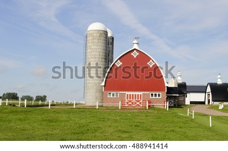 Vintage Wisconsin dairy farm with traditional red barn and silo's