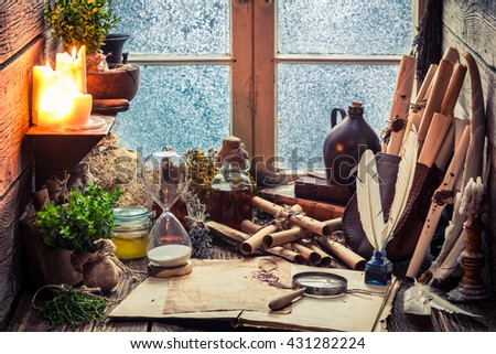 Vintage witch workshop with scrolls and ingredients - stock photo