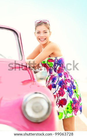 Vintage woman and car. Cute pink old vintage car and beautiful young retro woman smiling happy on sunny summer travel day. Pretty mixed race Asian / Caucasian female driver
