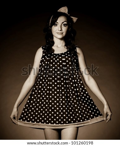 Vintage woman in retro dress on dark background. Pin-up girl - stock photo