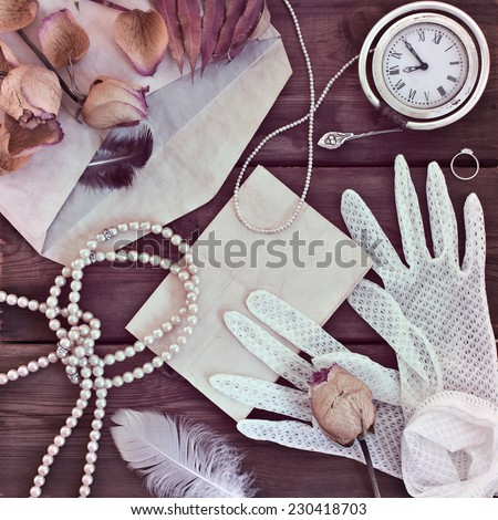 Vintage women's jewelry and gloves. Retro concept with dried roses on a wooden background