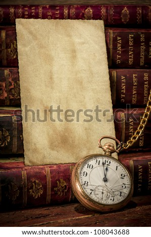 Vintage wood desk with old photo paper texture, books and old pocket clock showing a few minutes to midnight  in Low-key. Concept of time,the past or deadline. - stock photo
