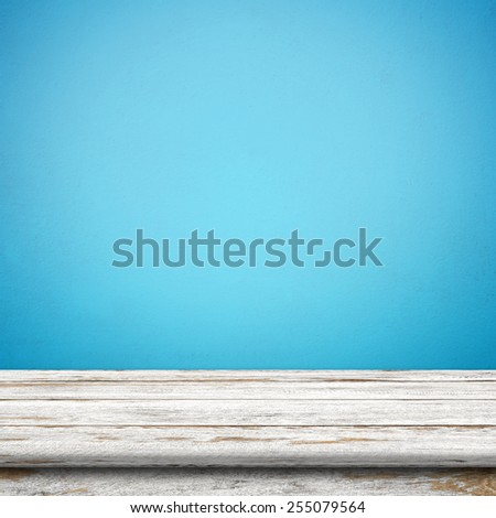 Vintage wood table in blue wall room. - stock photo