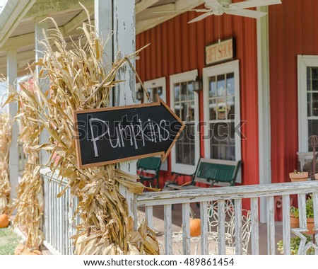 vintage wooden board with pumpkins word sign at entrance of red barn with dried corn stalks - Halloween Corn Stalks