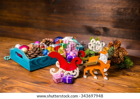 vintage wooden box with Christmas decoration, tinsel,  pinecones, stars, balls, sleigh, reindeer and gifts on wooden background, closeup  - stock photo