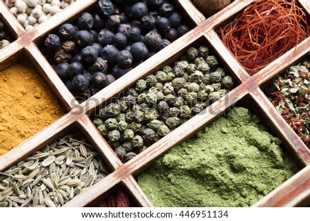 vintage wooden box with colorful spices, over old wooden table, sprinkled with spices, abstract compositions