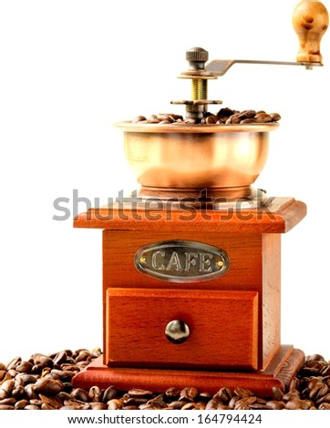 Vintage wooden coffee grinder full of roasted coffee beans