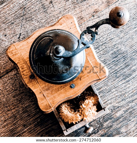 Vintage wooden coffee mill grinder with yellow flowers in open drawer - on the wooden table - stock photo