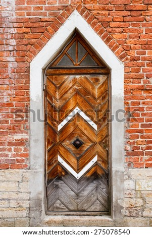 Vintage wooden door and old brick wall. Exterior details of a house of 18th century - stock photo