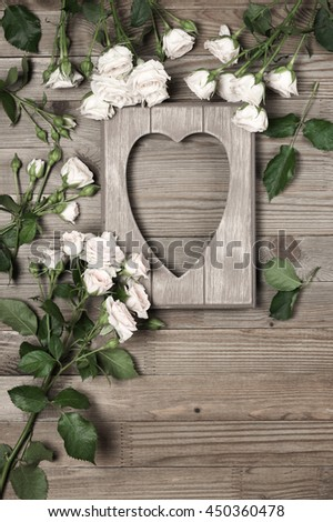 Vintage wooden heart shape photo frame with fresh light roses on rustic wood background. Top view point, flat lay. - stock photo