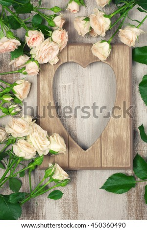 Vintage wooden heart shape photo frame with fresh pink roses on painted rustic wood background. Top view point, flat lay. - stock photo