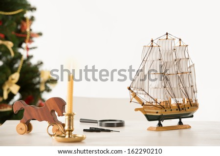 Vintage Wooden Horse and Ship on Santa's work table, Christmas Tree on background - stock photo
