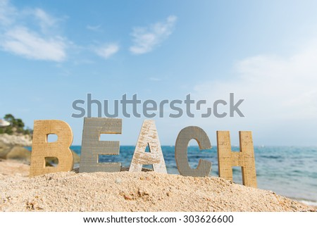 vintage wooden letters with word at the beach - stock photo
