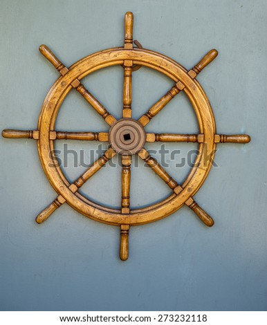 Vintage wooden ship wheel against a gray background. - stock photo