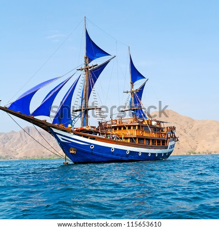 Vintage Wooden Ship with Blue Sails near Komodo Island, Indonesia - stock photo