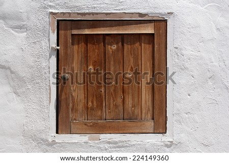 vintage wooden shutter in whitewashed wall - stock photo