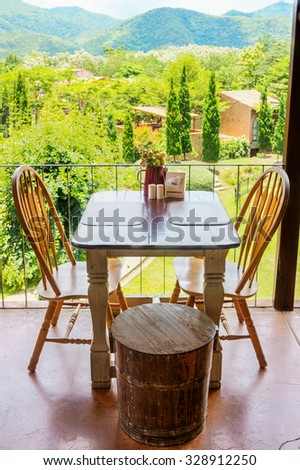 Vintage wooden table and chair on terrace with mountain view. The decoration of a restaurant.