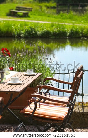 Vintage Wooden Table, with White Coffee Cups, and Chairs on Water Side Perfect Place for Date. Captured Outdoor on One Fine Morning.
