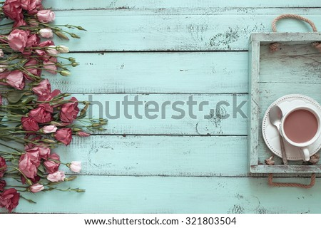 Vintage wooden tray with porcelain teacup and pink flowers on shabby chic mint background, top view point - stock photo