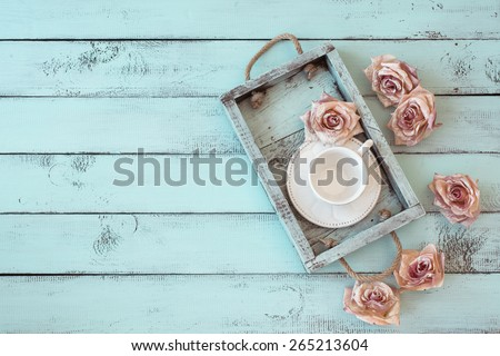 Vintage wooden tray with porcelain teacup and rose buds on shabby chic mint background, top view point - stock photo