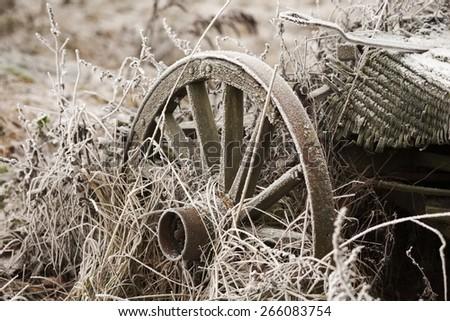Vintage wooden wheel in winter frost scenery - stock photo