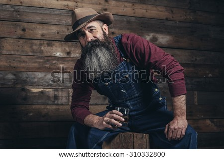 Vintage worker man with long gray beard in jeans dungarees holding whiskey. Sitting on wooden crate in barn. - stock photo