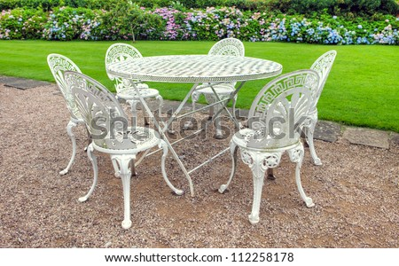 Vintage wrought iron garden table and six chairs in an English garden. - stock photo