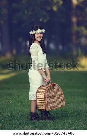 vintage young girl with picnic basket - stock photo