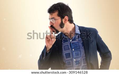 Vintage young man making silence gesture over ocher background