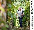 Vintner walking in his vineyard spraying chemicals on his vines - stock photo