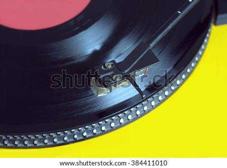 Vinyl LP record with red label sound reproduction on vintage turntable record player with yellow case. Horizontal photo from above closeup - stock photo