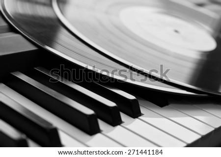 Vinyl record close up lying on piano keys - stock photo