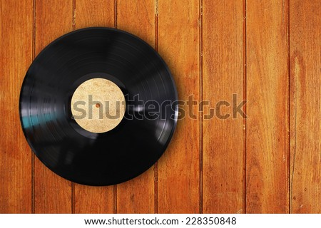 vinyl record in wood background - stock photo