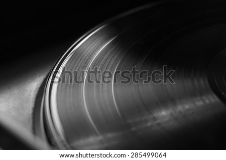 Vinyl record on a turntable with selective light and focus. Black and white photograph - stock photo