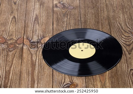 Vinyl record on wooden table in the closeup - stock photo