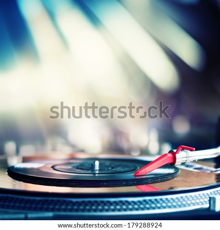 Vinyl record spinning on DJ turntable - stock photo