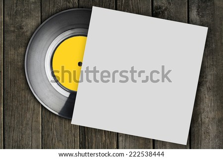 vinyl record with plain white packaging on wood surface - stock photo