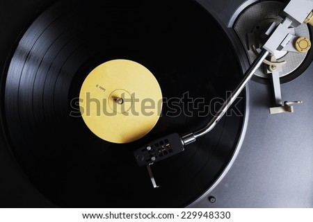 Vinyl record with yellow label playing on a turntable. Overview shot - stock photo
