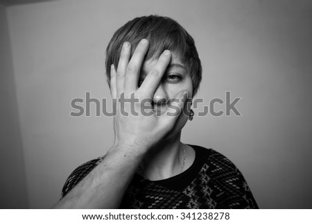 Violence against woman - young lady's face covered with man's palm - stock photo