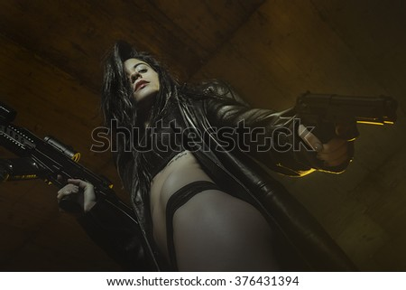 violence, brunette girl dressed in black leather with guns and pistols in a garage, scene of action - stock photo